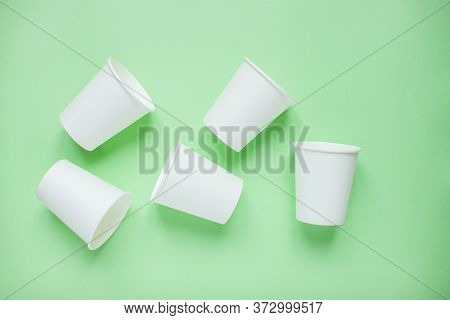 The Layout On A Green Background From White Paper Disposable Cups. Caring For The Environment. Recyc