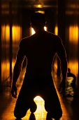 Silhouette of a sexy mysterious man with good body in glowing retro hallway poster
