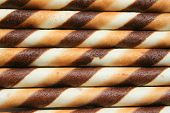 Close up of chocolate cookie sticks on a plate. poster