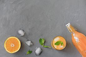 Orange And Orange Juice In A Bottle And In A High Glass. Mint Leaves On Grey Background. Ice Cubes M