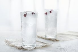 Two Glasses With Crushed Ice And Black Currant Berries On White Background In Blur.