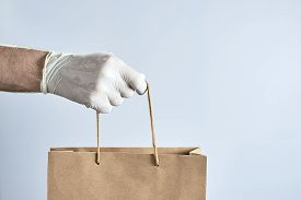 Hand In White Rubber Gloves Holds A Paper Bag. Photo With Copy Space. Concept Of Security During A P
