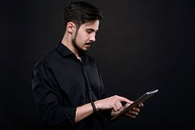 Serious young bearded man standing against black background and analyzing data on tablet