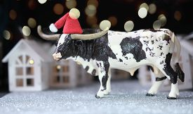 Toy Bull As Symbol Of 2021 Year. Happy New Year Concept. The Ox And Toy Houses With Bokeh Lights. Co