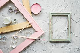 Several Wooden Frames, Paint Brushes And Paint Cans On Gray Gray Background. Workshop Of The Artist.