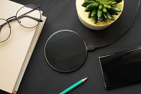 Wireless Charging On A Black Slate With A Book, Pencil, Smartphone, Glasses And A Plant.