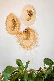 Three Straw Wicker Hats On A White Wall.