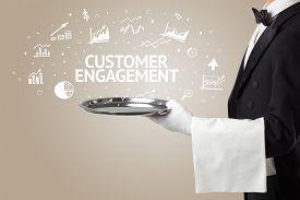 Waiter serving business idea concept with CUSTOMER ENGAGEMENT inscription