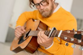 Bearded young musician with string musical instrument making music or tuning acoustic guitar in home environmeny before playing it
