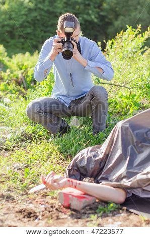 Young Criminalist Takes Picture Of Crime Scene