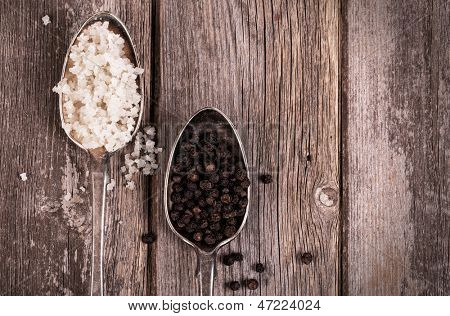 Vintage effect image of tarnished silver spoons filled with salt crystals and black peppercorns, over rough wood background.