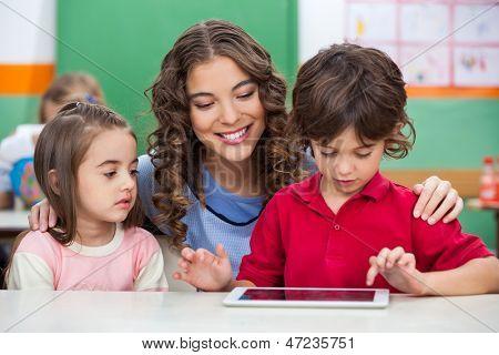 Niños usando tableta digital con el maestro en el aula