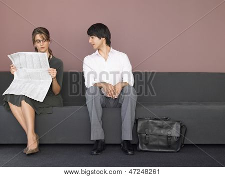 Young businesswoman reading newspaper sitting beside male colleague on sofa
