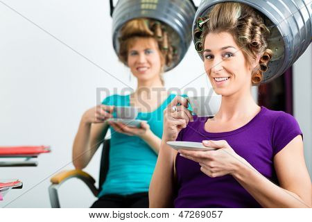 women at the hairdresser drinking coffee or cappuccino and chit-chat, while your hair drying under a hairdryer
