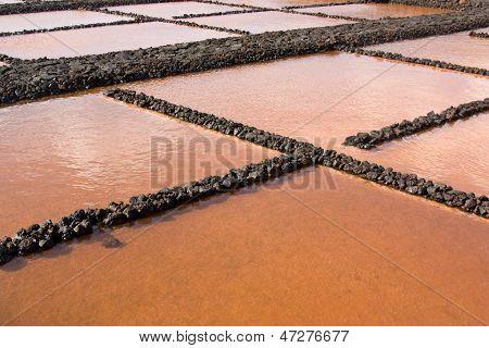 Salt evaporation pond in La Palma Canary Islands. Orange color is due to photosynthetic algae. poster