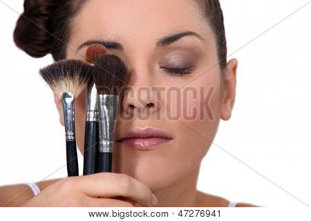 Woman holding various make-up brushes