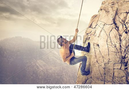 brave young man climbs a mountain