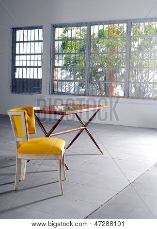 Empty Yellow Chair And Table In Minimalist Loft