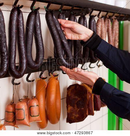 Butcher Arranging Sausages On Hooks