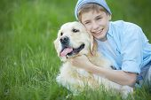 Portrait of cute lad embracing his fluffy friend while lying on grass poster