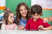 Children using digital tablet with teacher at classroom desk poster