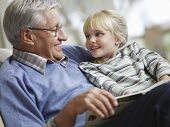 Happy little girl with grandfather reading story book at home poster