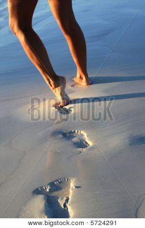 Woman legs on sandy beach