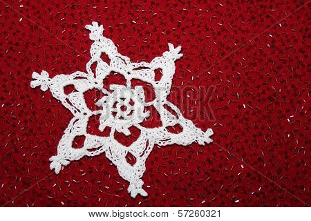 Crochet Snowflake on Red Bead Background