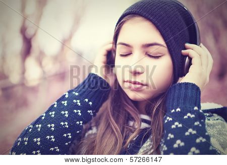 Teenage Girl In Headphones Listens To Music With Closed Eyes