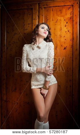 Beautiful brunette woman in white sensual lace outfit posing provocatively in front of a wooden wall
