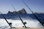 Fishing rod and reel on boat in mediterranean blue ocean poster