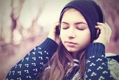 teenage girl in headphones listens to music with closed eyes outdoors poster