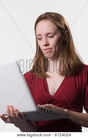 a young woman looks down at her laptop computer screen with a disconcerted look on her face poster