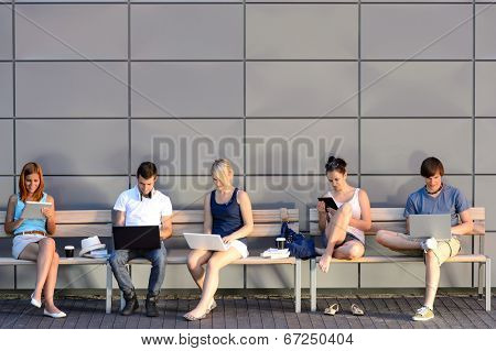College students internet computer addiction sitting bench outside campus summer