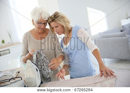 Elderly woman with housekeeper ironing clothes