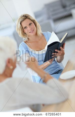 Homecarer reading book to elderly woman