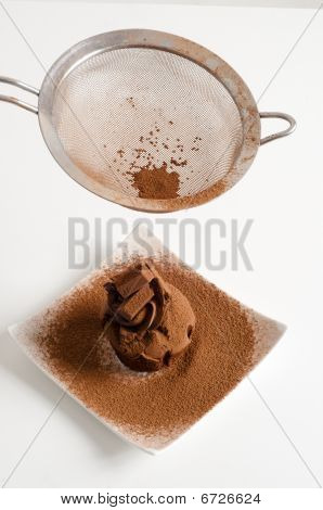 Sieving Coco Powder Onto Chocolate Muffin On Plate