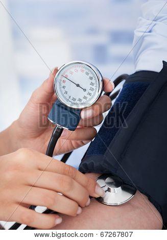 Doctor Checking Blood Pressure Of Businessman