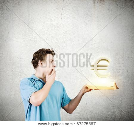 young man in casual holding opened book with euro sign poster