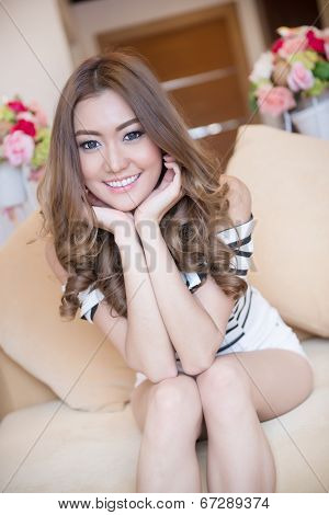 Young Beautiful Woman Is Sitting On Sofa Happily