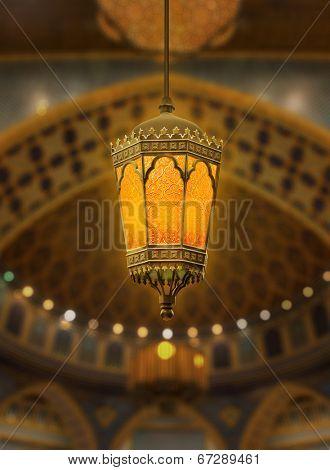 An illuminated Ramadan lantern against islamic architecture