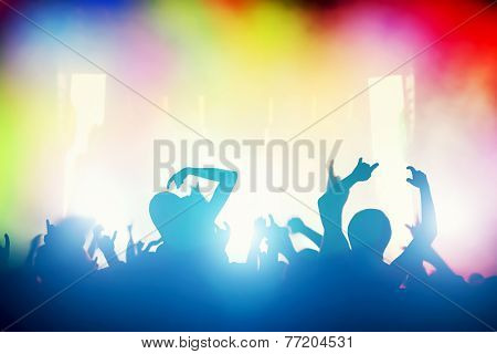Concert, disco party. People with hands up having fun in night club lights