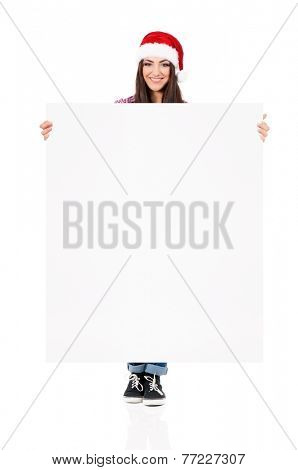 Happy smiling girl in Santa Claus hat showing blank signboard, isolated on white background
