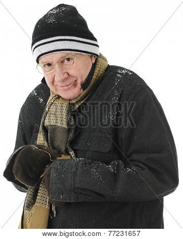Closeup image of a bundled but shivering senior man smiling at the viewer.  On a white background.