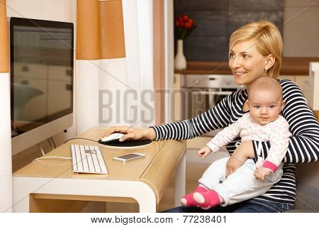 Young mother working on computer while holding baby girl on lap, smiling.