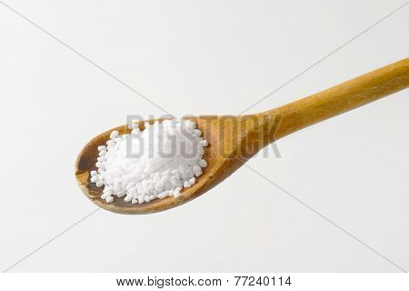 wooden spoon of granular salt