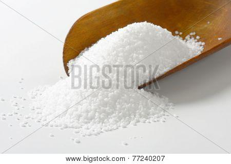 detail of sea salt heap on the wooden measuring spoon