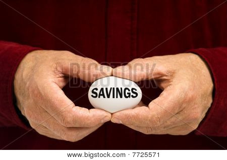 Man Holds White Egg With Savings Written On It