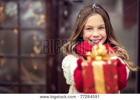 Child giving a Christmas present near her house door, snowy outside