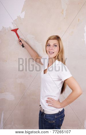 handywoman removing wallpaper